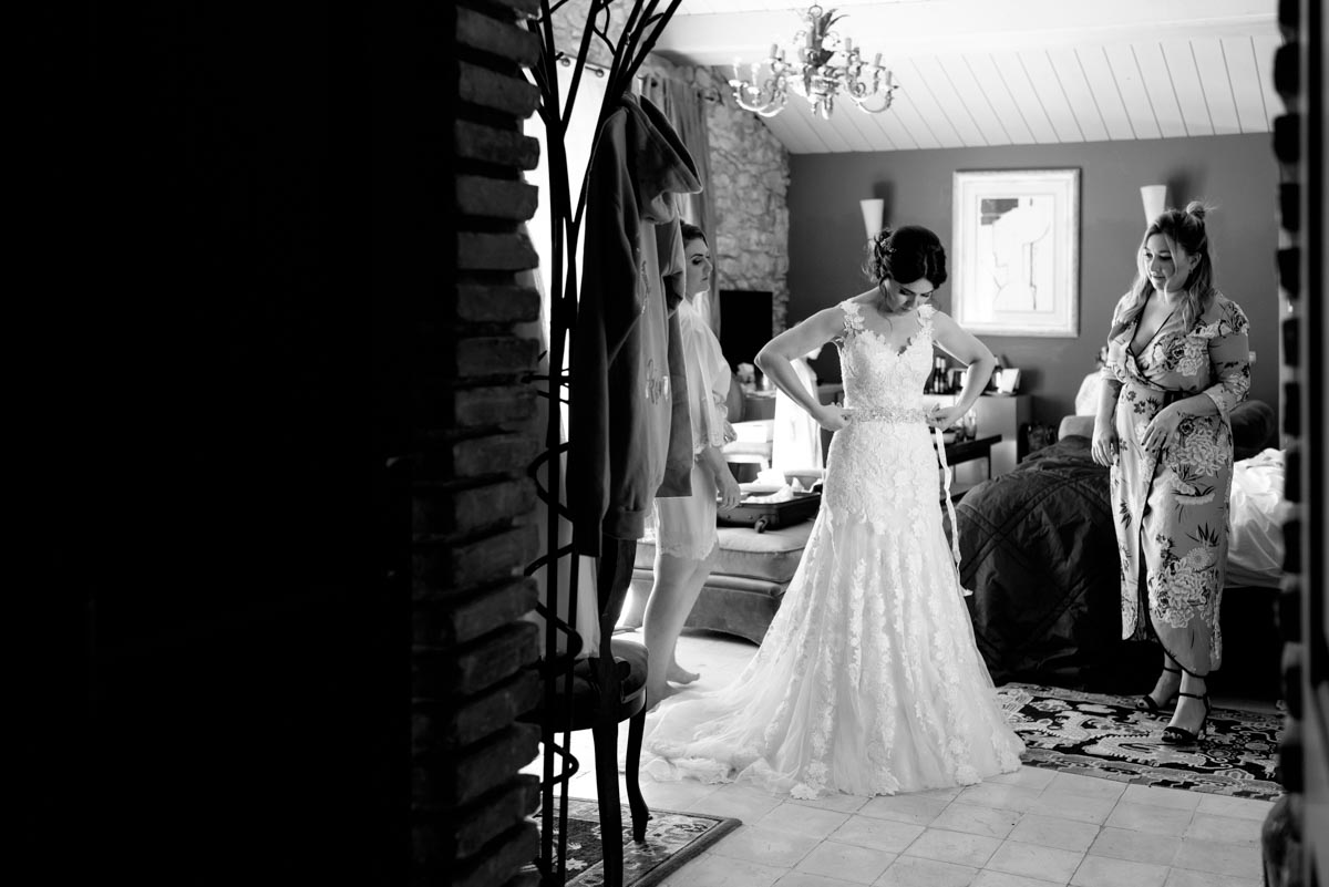 Photograph of Rebecca putting the finishing touches to her wedding dress