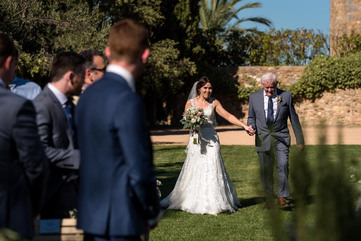 Rebecca is walked up the aisle on her wedding day at castell d'emporda