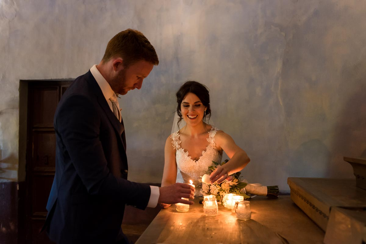 rebecca and matt light candles in chapel at castell d'emporda wedding venue