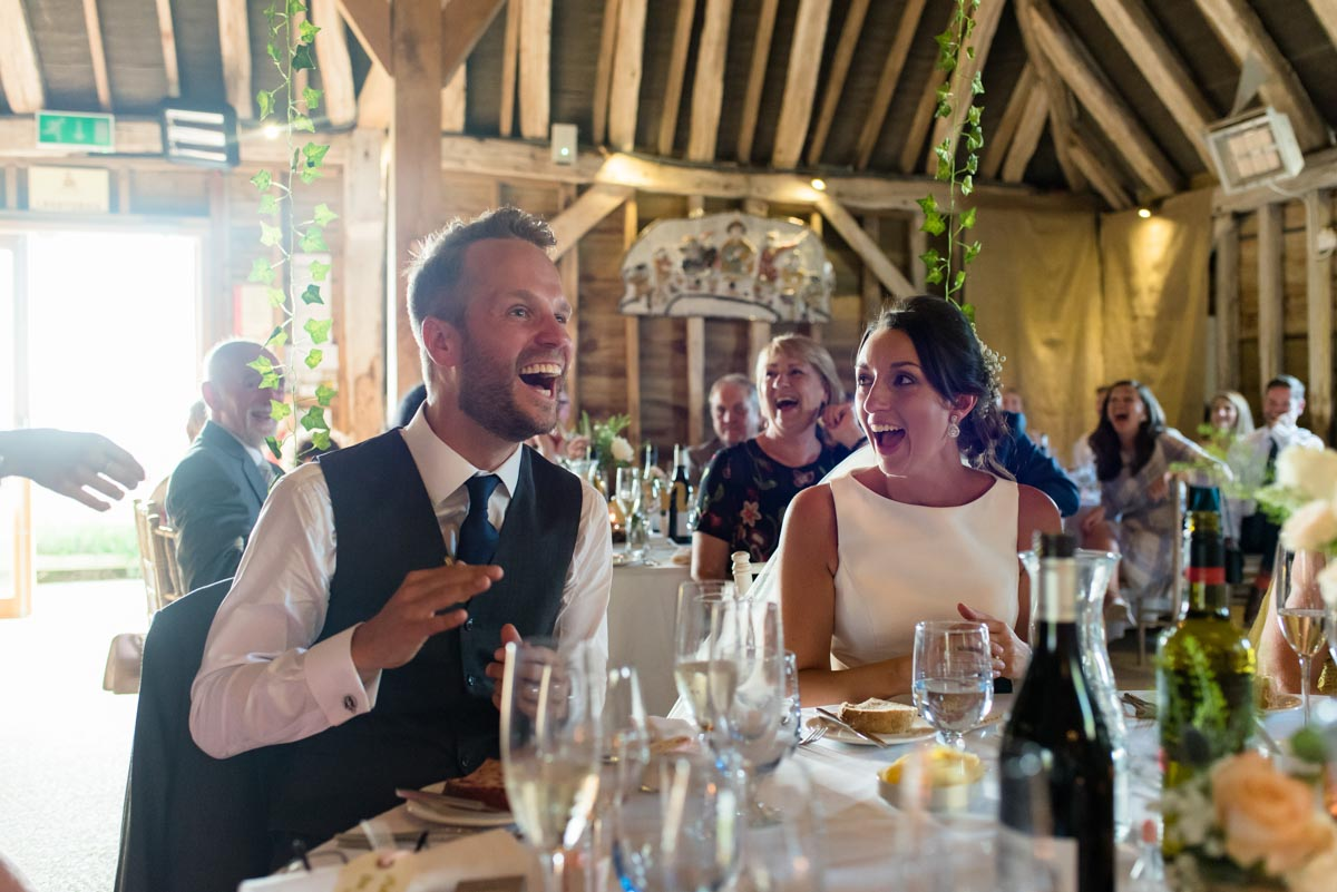 Sarah and Craig laughing during wedding speeches at odo's Barn in Kent
