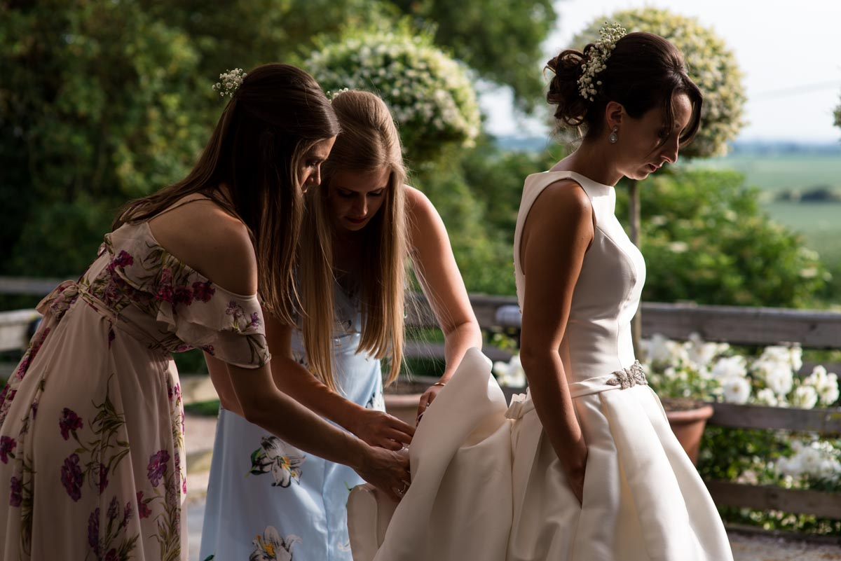 Bridesmaids adjust Sarah's wedding dress at Odo's Barn in Kent