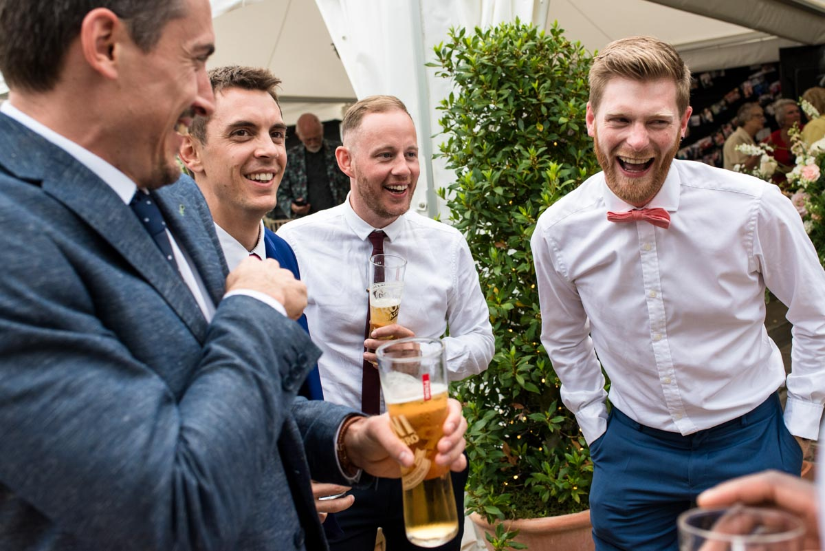 Guests laughing together at Sarah and Craigs wedding at Odo's Barn in Kent
