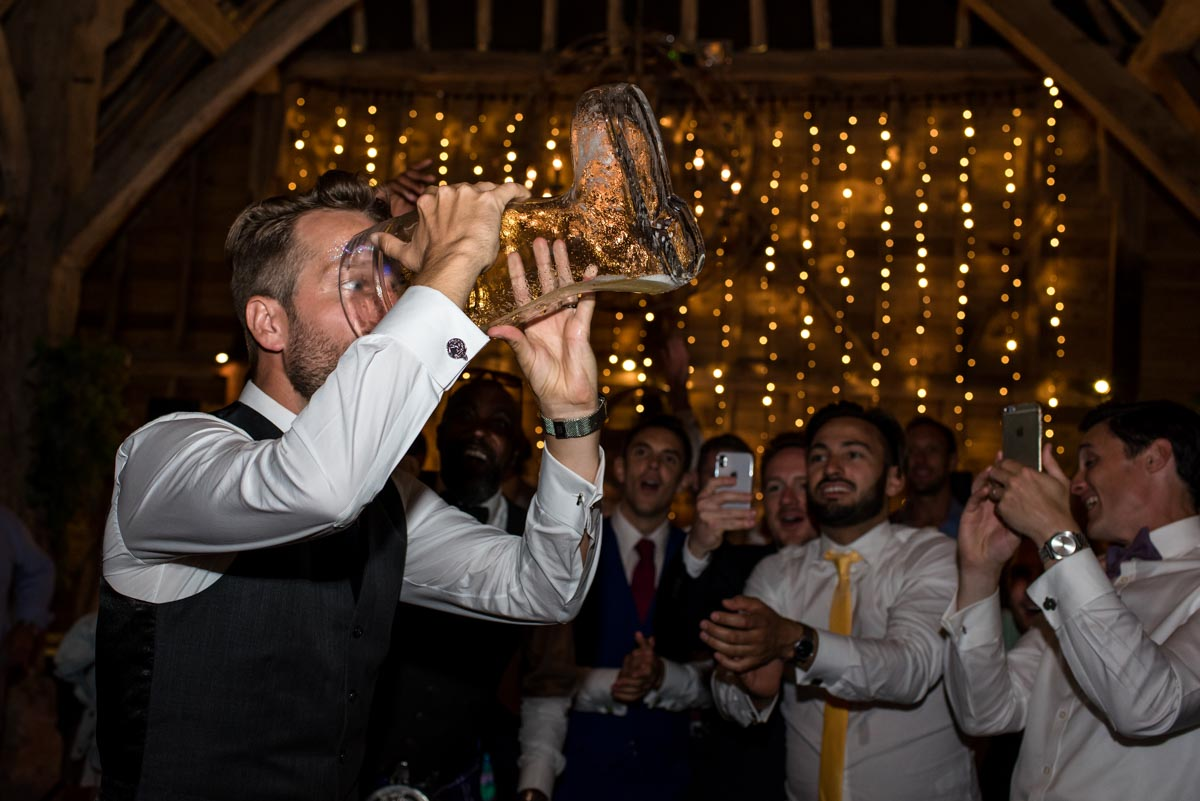 odo's Barn wedding photography, Craig drinks from the beer boot