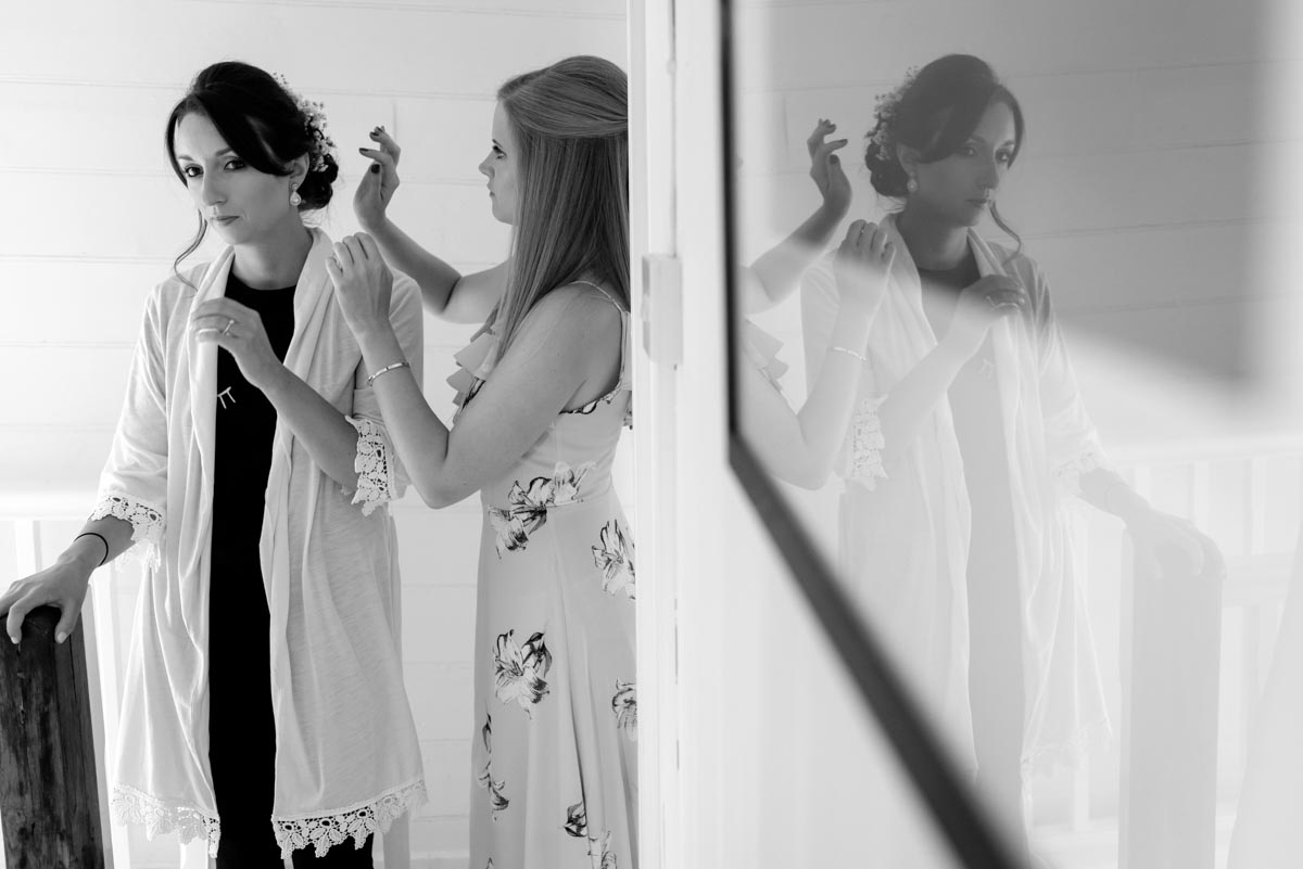 Bridesmaid makes finishing touches to sarahs hair before her wedding at Odo's Barn in Kent