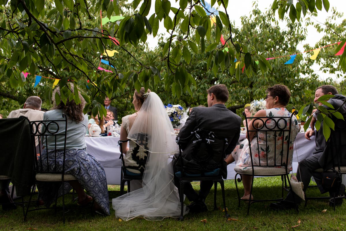 Photograph of Hannah and Matthew at the top table in the orchard for their Kent wedding reception