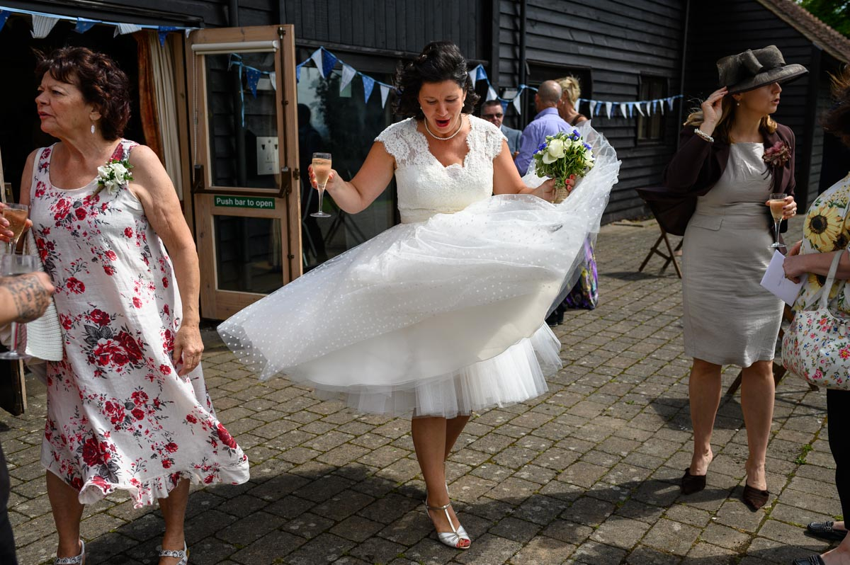 Nathalies wedding dress lifts in the wind during her Kent wedding reception