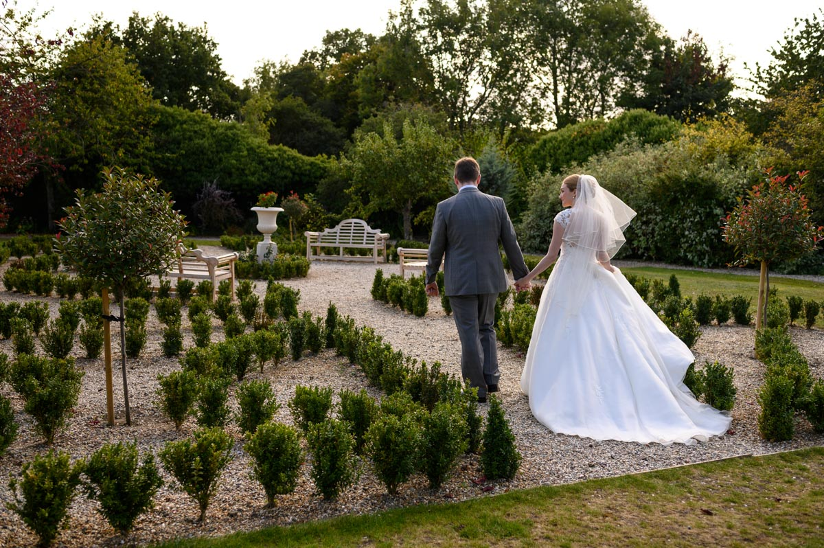 Jack & Bethany walk through gardens at Secret Garden wedding in Kent