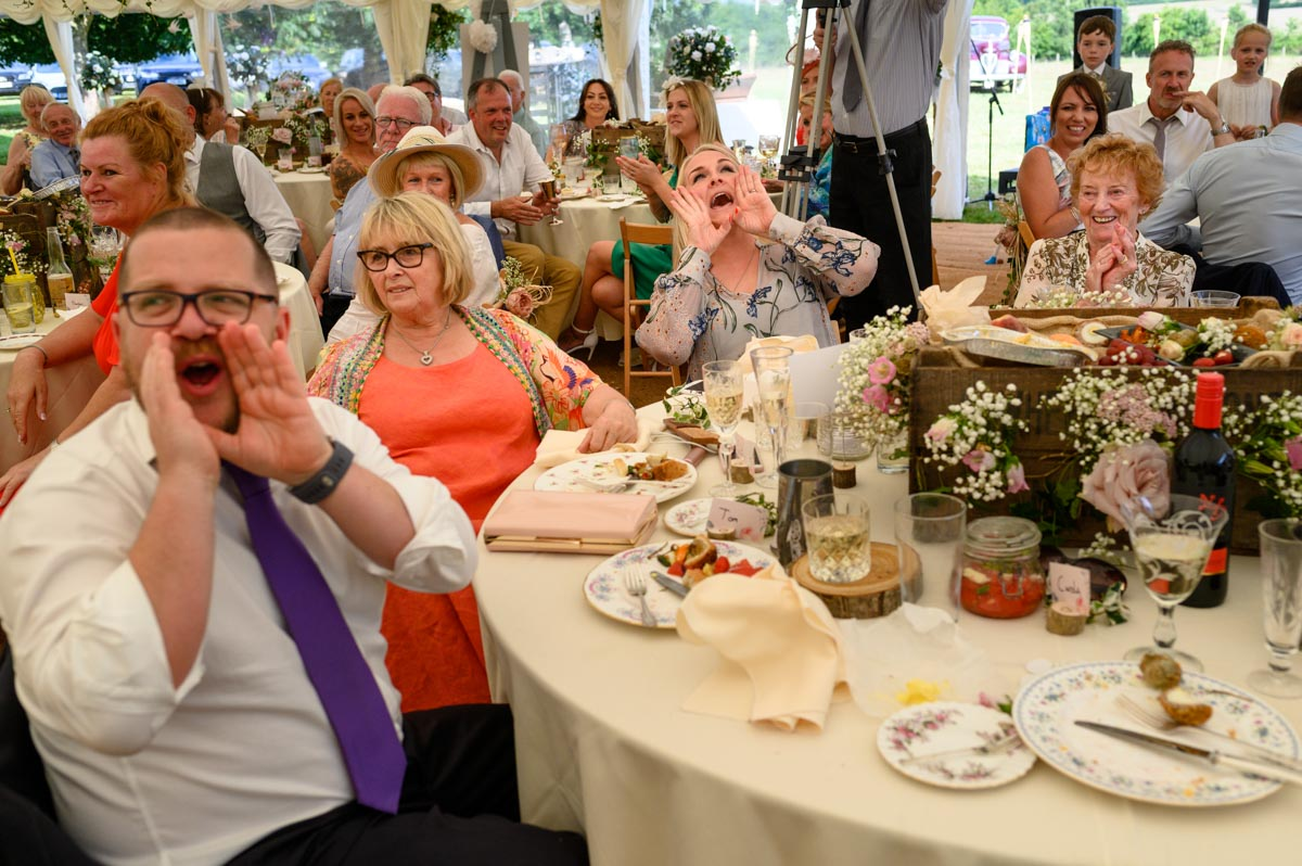 Summer wedding guests enjoy speeches and shout for more