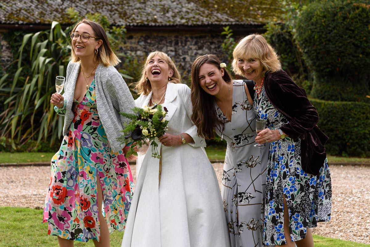 Bride and wedding guests photographed laughing at Solton Manor wedding