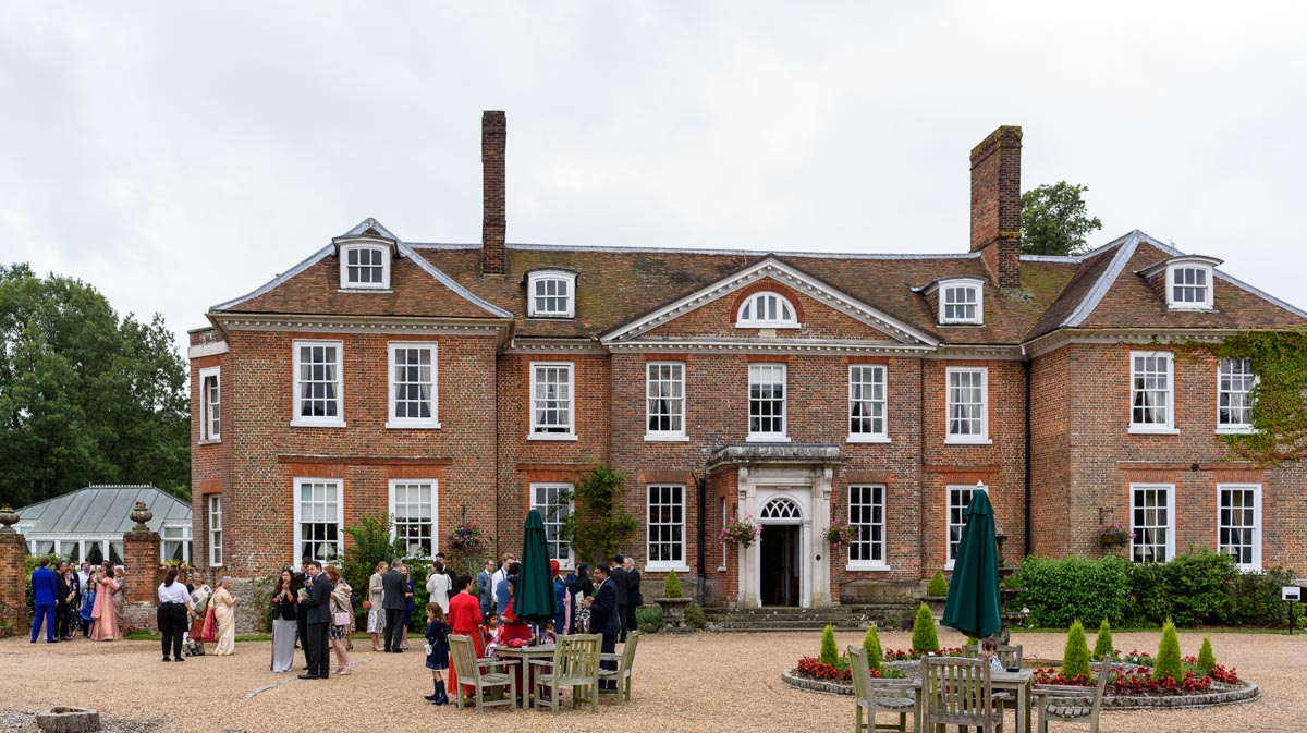 Guests enjoy drinks outside Chilston park hotel during Doug and Vinitas wedding reception