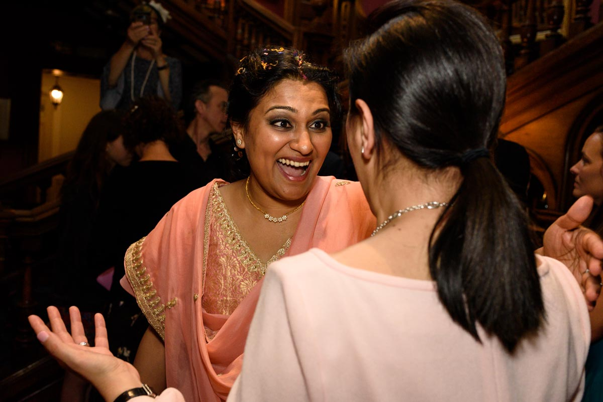 Vinita photographed laughing with friend at her wedding in Kents Chilston park
