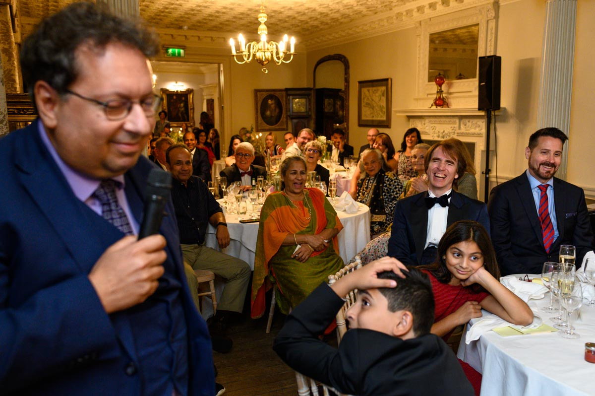 Guests enjoy speech at Doug and Vinitas wedding at Chilston Park in Kent