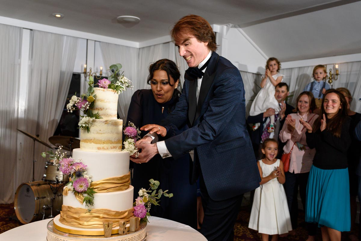 Doug and Vinita cutting their wedding cake at Chilston Park in Kent