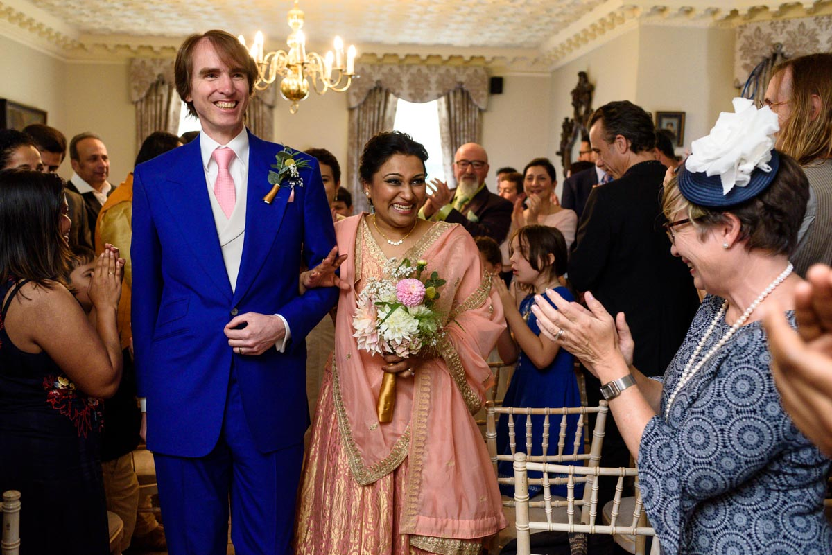 Newly weds Doug and Vinita walking down the aisle after their Chilston park wedding ceremony